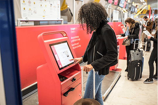 woman using check in kiosk at airport